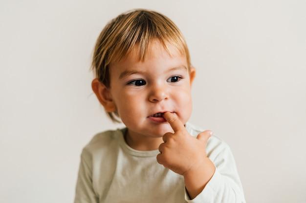 Enfant en bas âge avec un doigt dans la bouche. concept de dentition ronflement gencives