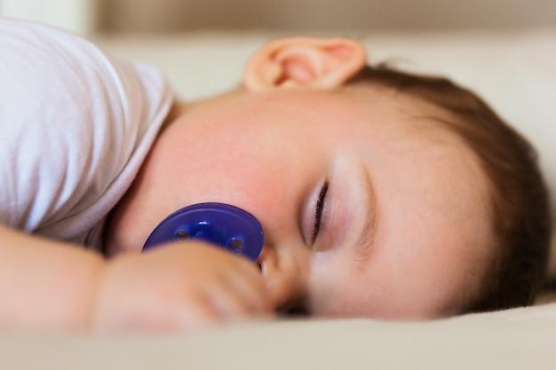 Enfant en bas âge dormant sur le lit.