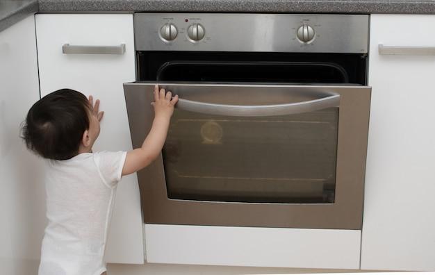 Enfant en bas âge joue devant la cuisine ouverte à la maison dans la cuisine