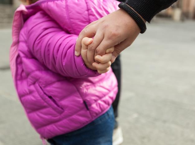 Enfant en bas âge, main dans la main avec sa mère