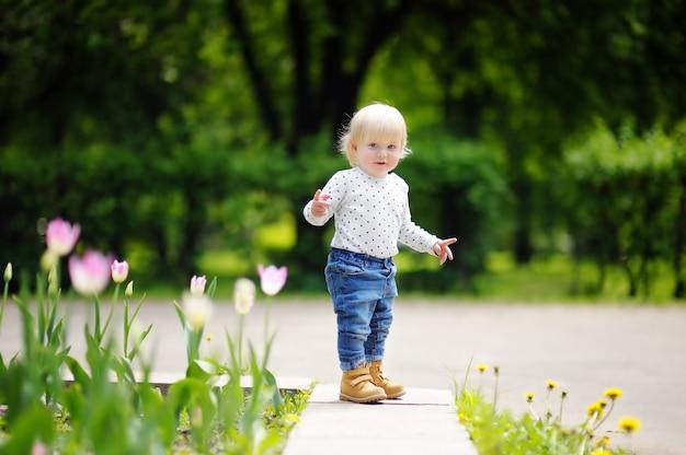 Enfant en bas âge marchant dans le jardin au printemps ou en été