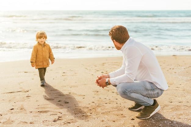 Enfant en bas âge marchant sur la plage avec papa