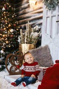 Enfant en bas âge mignon dans le chandail laid posant sur les escaliers de la maison décorée pour noël