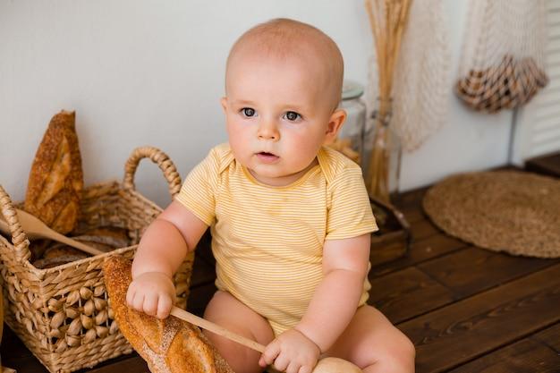 Enfant en bas âge mignon dans la cuisine en bois de la maison