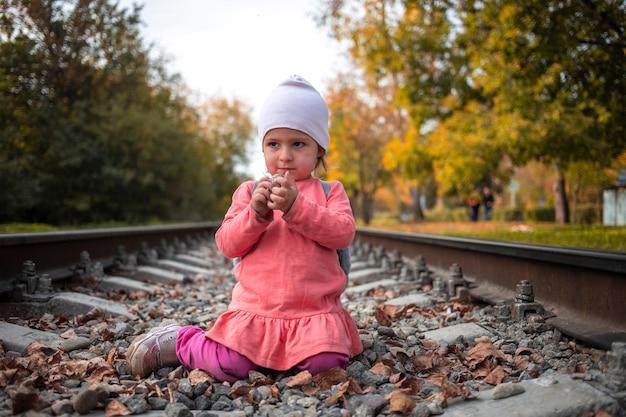 Enfant en bas âge mignon jouant avec des pierres sur les jeux dangereux de remblai de chemin de fer