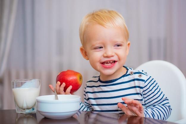 Enfant en bas âge mignon mangeant son repas, tenant une pomme dans sa main, souriant.