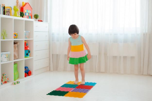 Enfant en bas âge sur le tapis de massage de pied de bébé. exercices pour les jambes sur tapis de massage orthopédique. prévention des pieds plats et de l'hallux valgus