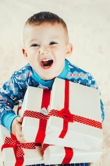 Un enfant avec beaucoup de cadeaux, le réveillon du nouvel an criant de joie, les tenant dans ses mains