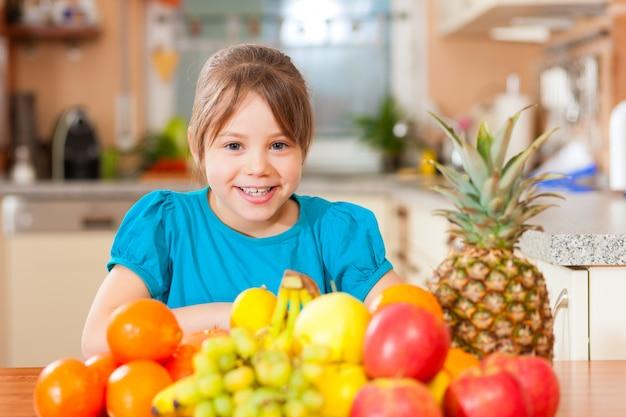 Enfant avec beaucoup de fruits pour le petit-déjeuner