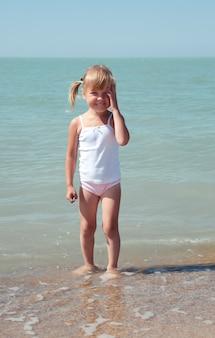 Enfant de beauté en mer sous le ciel bleu