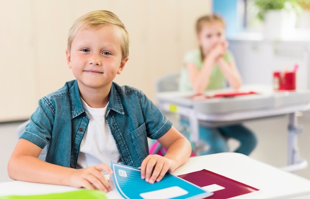 Enfant blond assis à son bureau
