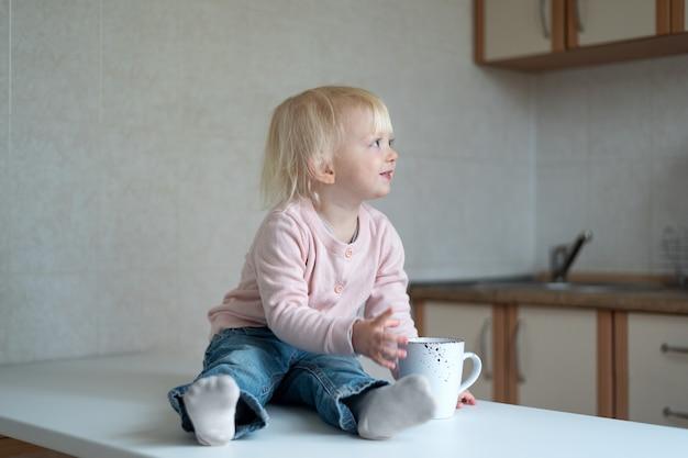 Enfant blond dans la cuisine avec une tasse dans ses mains. portrait de tout-petit dans la cuisine.