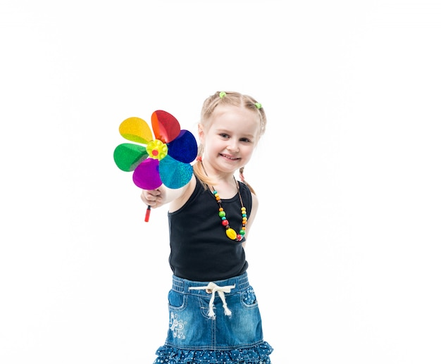 Enfant blond souriant avec jouet en rotation portant débardeur