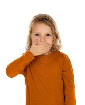 Enfant blond surpris aux yeux bleus couvrant sa bouche