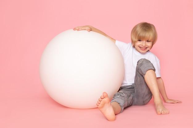 Un enfant blond vue de face en t-shirt blanc jouant avec une boule blanche ronde sur l'espace rose