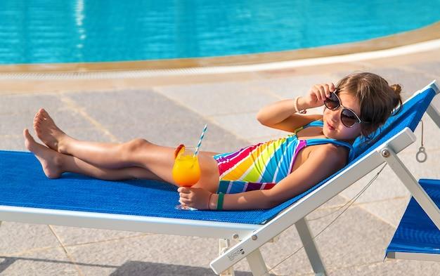 L'enfant boit un cocktail au bord de la piscine