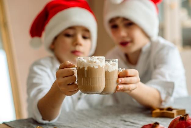 L'enfant boit du chocolat chaud de noël à la maison. les familles avec enfants célèbrent les vacances d'hiver.