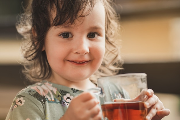 L'enfant boit du thé en gros plan sur le visage de l'enfant, une petite fille douce regarde dans le cadre et sourit...