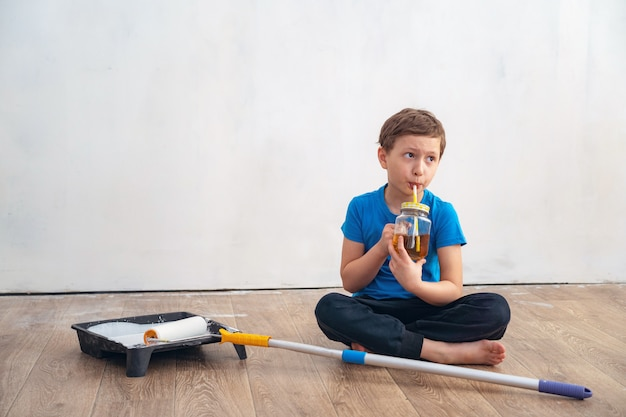 L'enfant boit du thé pendant la réparation du mur.