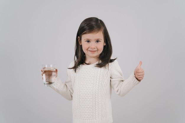 L'enfant boit de l'eau dans un verre. une fille aux cheveux noirs tient un verre d'eau. la brune mène une vie saine