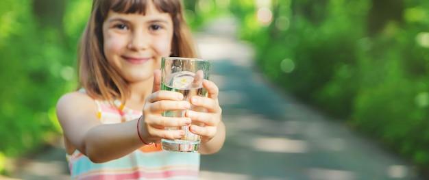 Un enfant boit de l'eau dans un verre sur la nature