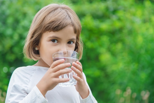 Enfant boit de l'eau dans un verre