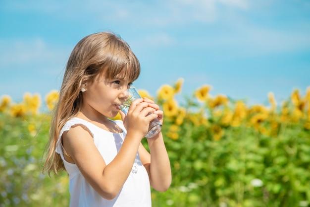 Un enfant boit de l'eau sur le fond du champ