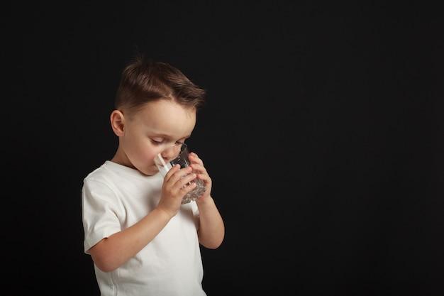 Un enfant boit de l'eau sur un fond noir