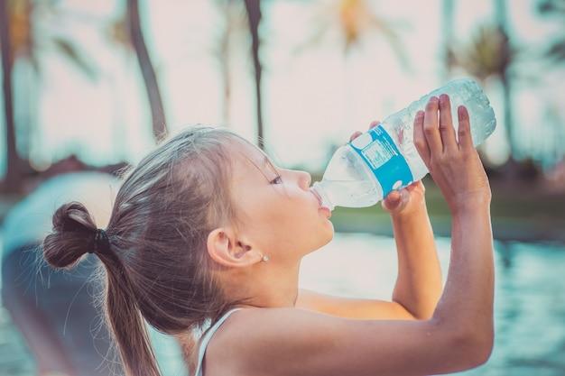 Un enfant boit de l'eau propre dans une bouteille. chaude journée d'été.