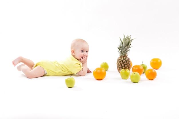 Un enfant en bonne santé souriant se trouve parmi des fruits