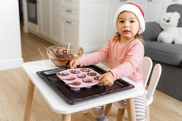 Enfant en bonnet de noel, préparer des biscuits de vacances à la maison. activité de noël à la maison pour tout-petit