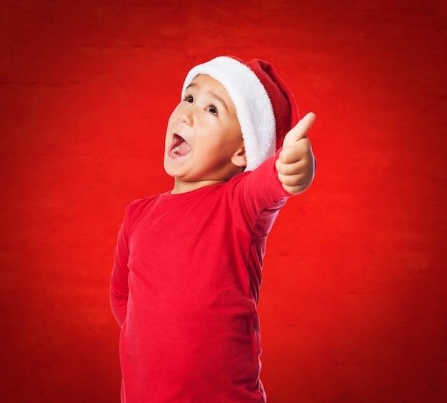 Enfant avec la bouche ouverte et le chapeau de père noël