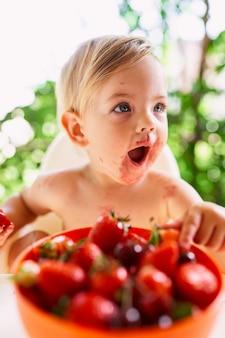 L'enfant avec une bouche ouverte s'assied devant un bol de fraises