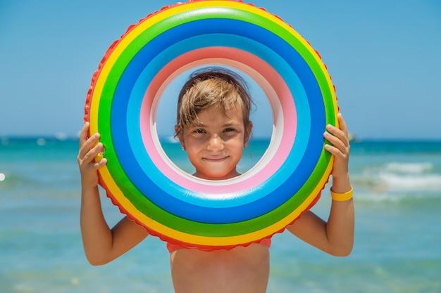 Enfant avec une bouée de sauvetage en mer.