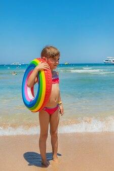 Enfant avec une bouée de sauvetage en mer