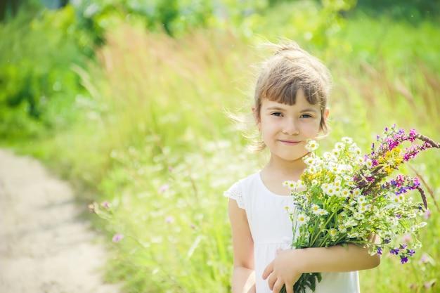 Enfant avec un bouquet de fleurs sauvages. mise au point sélective. la nature.