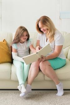 Un enfant avec un bras cassé et du gypse passe du temps à la maison avec des maladies infantiles de la mère positives
