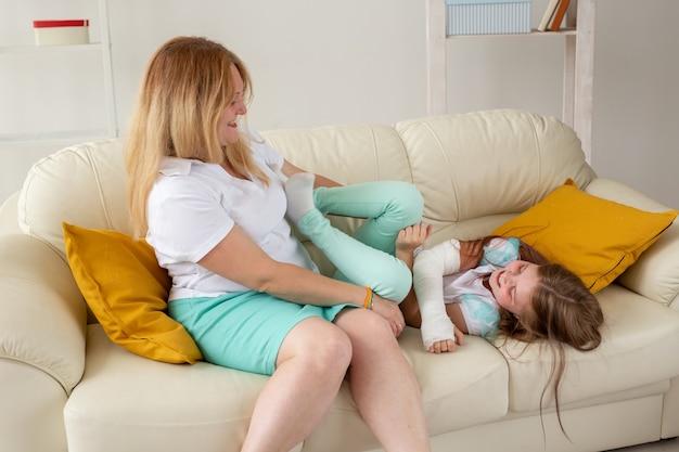Enfant avec bras cassé et gypse passer du temps à la maison avec sa mère