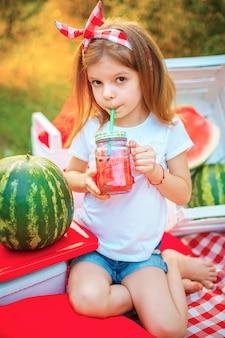 Enfant buvant de la limonade à la pastèque en pot avec de la glace et de la menthe comme boisson rafraîchissante d'été. boissons gazeuses froides aux fruits