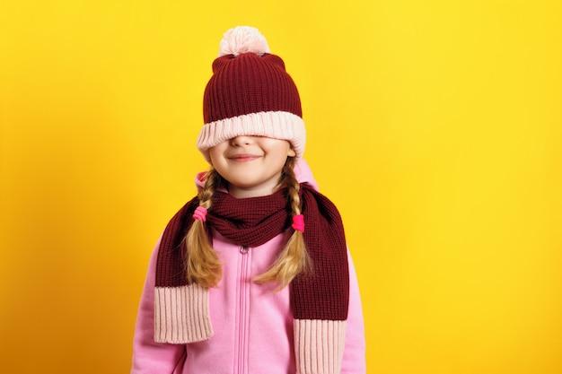 Enfant cache ses yeux sous un chapeau