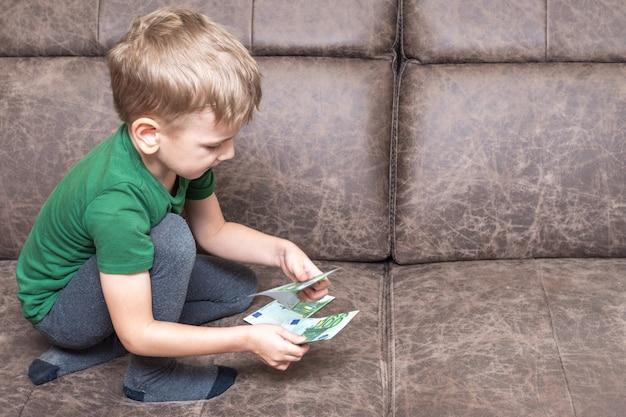 Un enfant caucasien concentré dans des vêtements décontractés tient cent euros dans ses mains et compte de l'argent sur le canapé de la pièce, vue latérale, espace de copie. l'éducation financière et économique des enfants