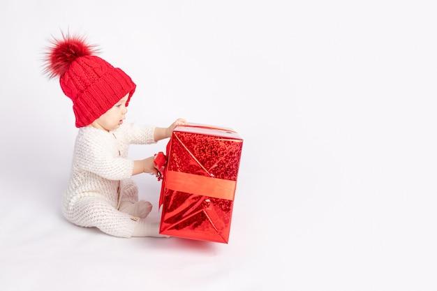 L'enfant avec le chapeau rouge et cadeau sur fond isolé blanc, espace pour le texte, le concept de nouvel an et noël