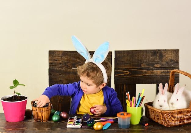 L'enfant chasse les œufs de pâques. achetez en ligne pour la décoration de joyeuses pâques.