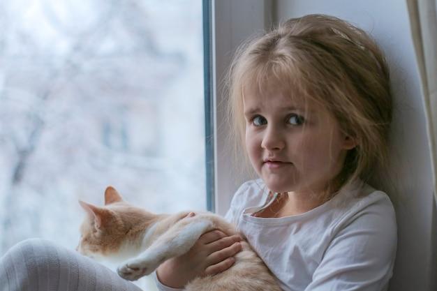Un enfant et avec un chat assis sur la fenêtre et jouant