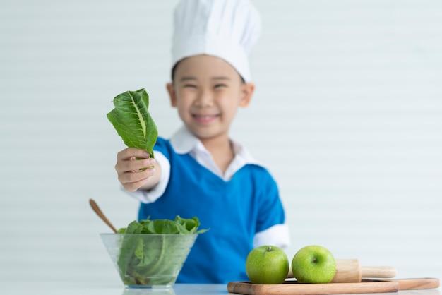 Enfant chef sont heureux avec des légumes frais