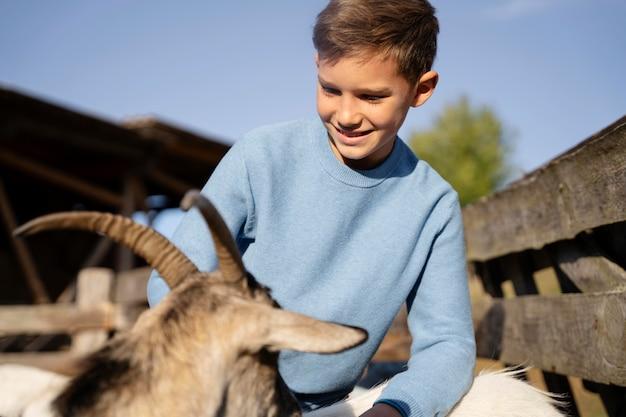 Enfant et chèvre smiley de plan moyen