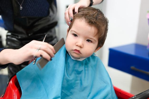 Enfant chez le coiffeur en gros plan. la première coupe de cheveux de l'enfant chez le coiffeur. bébé coupe de cheveux enfant en bas âge.