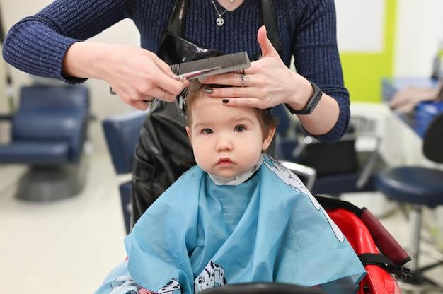 Un enfant chez le coiffeur. la première coupe de cheveux de l'enfant chez le coiffeur. bébé coupe de cheveux enfant en bas âge.