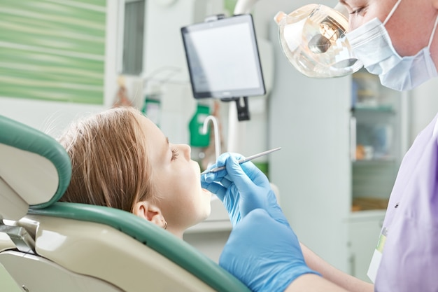 Enfant chez le dentiste. enfant dans le traitement dentaire du fauteuil dentaire pendant la chirurgie. petit enfant spécialiste de la visite des patients en clinique dentaire.