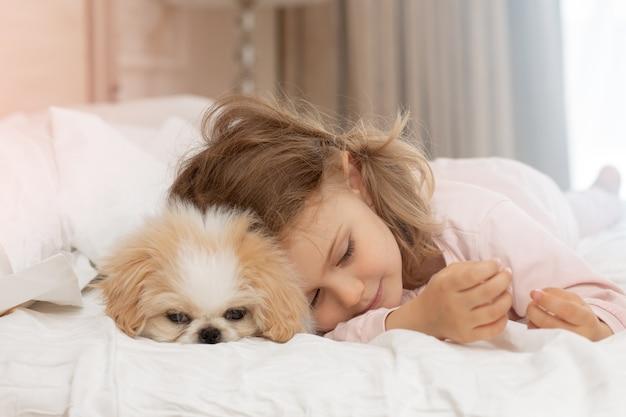 Enfant et chien chiot dorment sur le lit à la maison animal de compagnie et enfants d'amitié de soins aux animaux